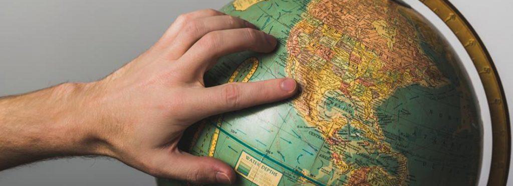 Main sur un globe terrestre